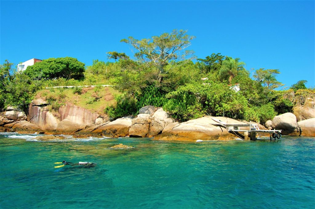 Photograph of a diver in the Bay of Paraty Brazil, clear waters with visibility 10 meters or more depending on day and season, natural light solar photography, spring season.