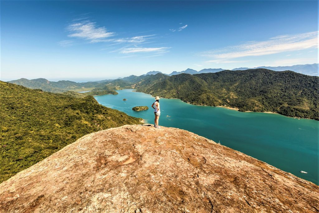 A DSRL photo taken at the top of a mountain beside the calm sea in Mamangua, Paraty, Rio de Janeiro, Brazil. At the very top there is a young woman contemplating the view. It is a sunny day with bright blue sky.