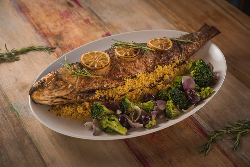 whole roasted mullet, brocolles, onions and dehydrated orange slices, on wooden table