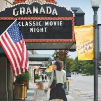 family walking past historic Granda Theatre marquee on Commercial Street in emporia