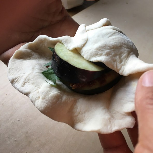Folding over the sides of the skin to seal the dumpling. This one is stuffed with eggplant slices, miso paste,  and shiso leaf