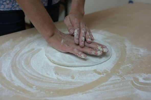Pressing the dough into a flat, round shape