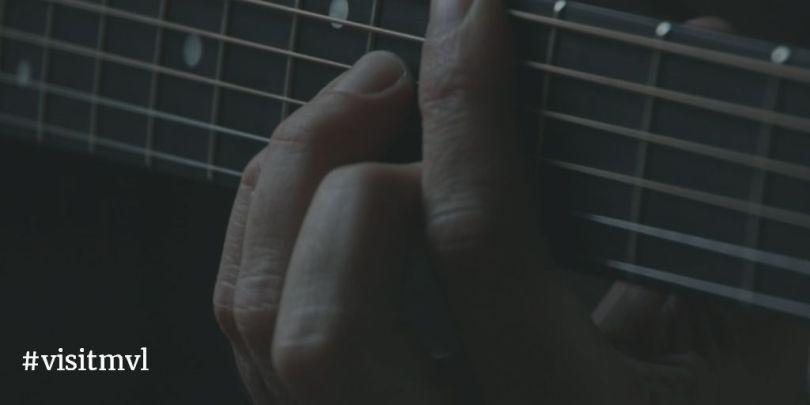 close-up playing guitar chord