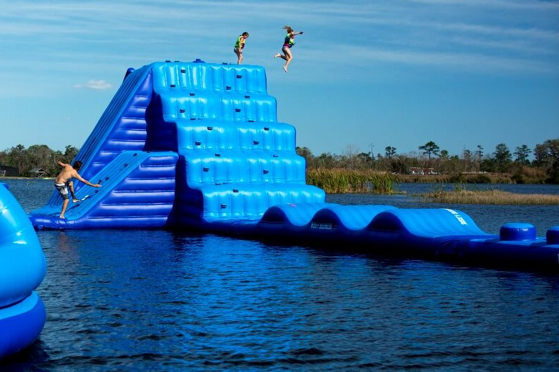 Aqua Park image. Man climbing up a large inflatable water piece of equipment while two other people jump off