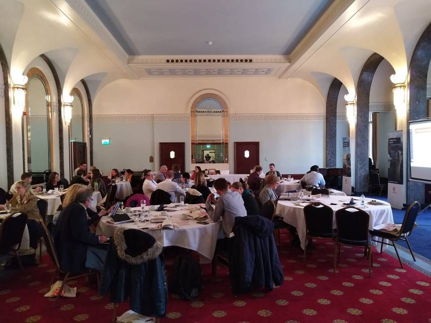 The image shows people seated at circular tables as part of a seminar at Portsmouth Guidlhall