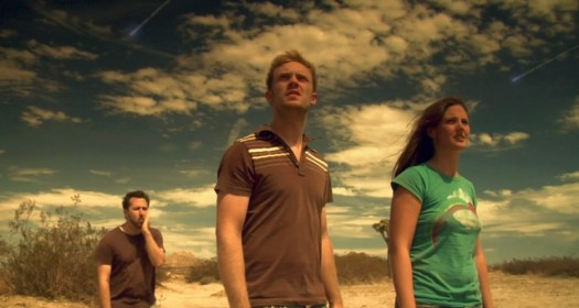 Three people standing in the desert as two small meteors pass overhead in Apocalypse CA (2011).
