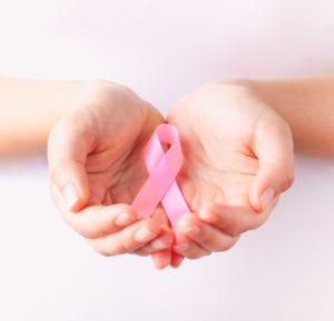 holding pink breast cancer awareness ribbon