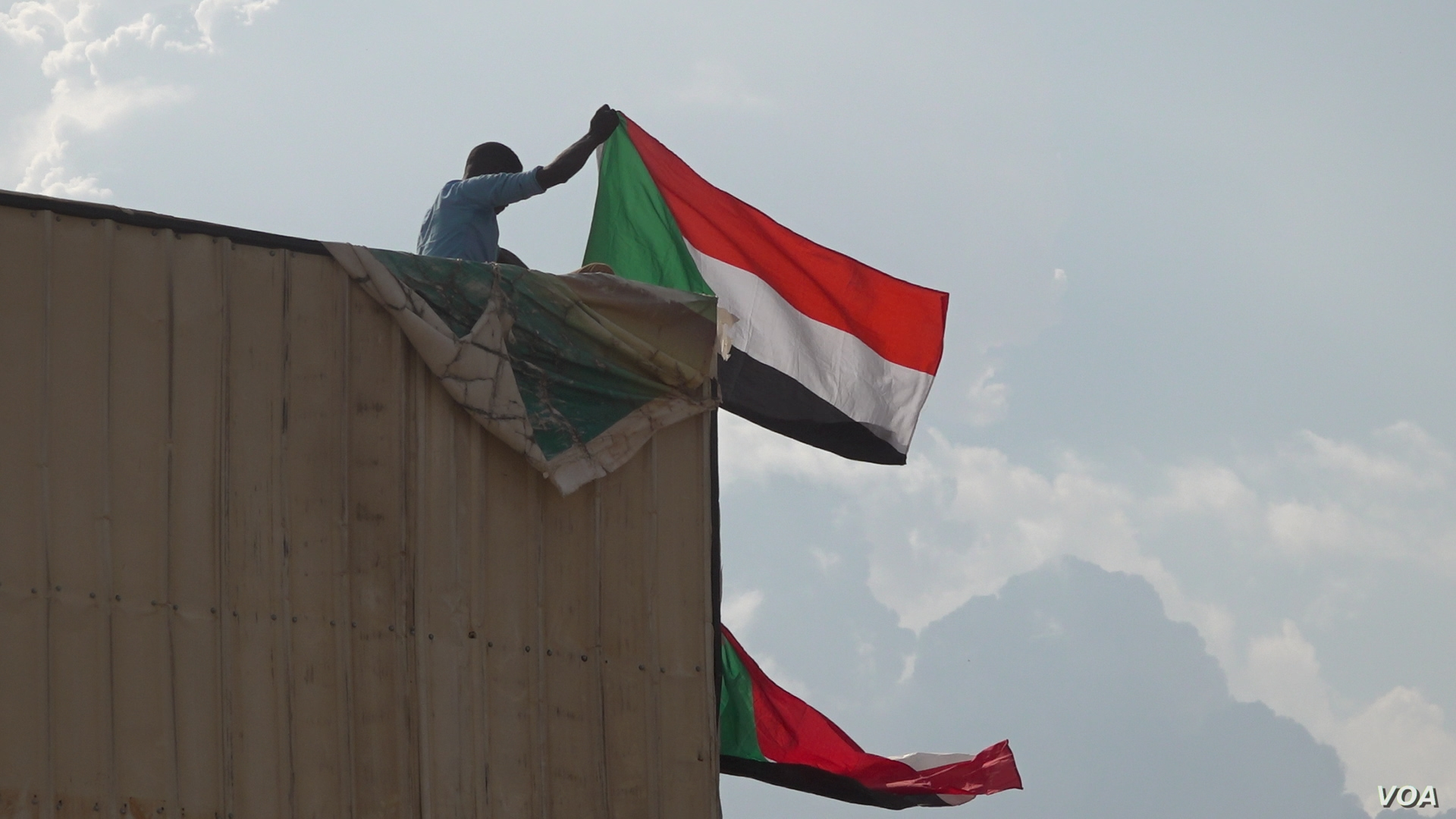 A man climbed a billboard in Khartoum to wave Sudan's flag in honor of the agreement signing (E. Sarai/VOA)