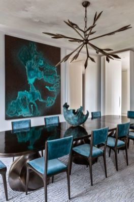 I love this gentle avant-garde dining room. The blue in the chairs and the art with the brutalist bowl all compliment the aggressive chandelier.