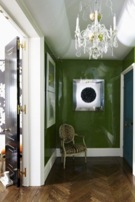 Todd Romano created a very sophisticated foyer in lacquered avocado with a rich teal blue door.