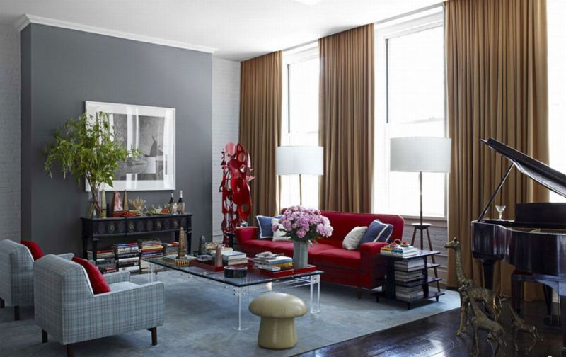 Bold colors with the deep cranberry sofa, gold curtains, and a pale sky blue rug with grey walls gently quiet the statement in a chic and sophisticated way.