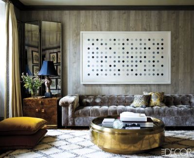 The round brass cocktail table is the perfect compliment to the Damien Hirst piece above the sofa.