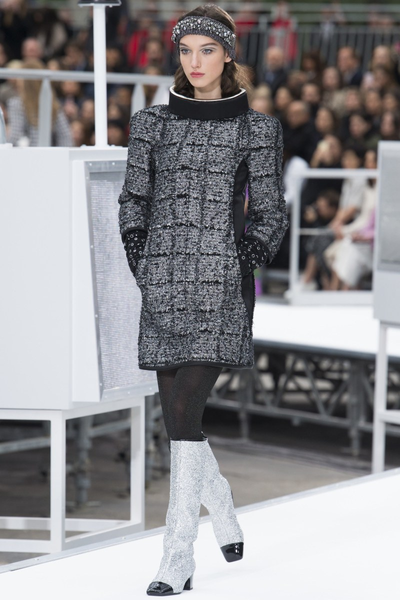model wearing black and gray coat walks down runway at chanel show