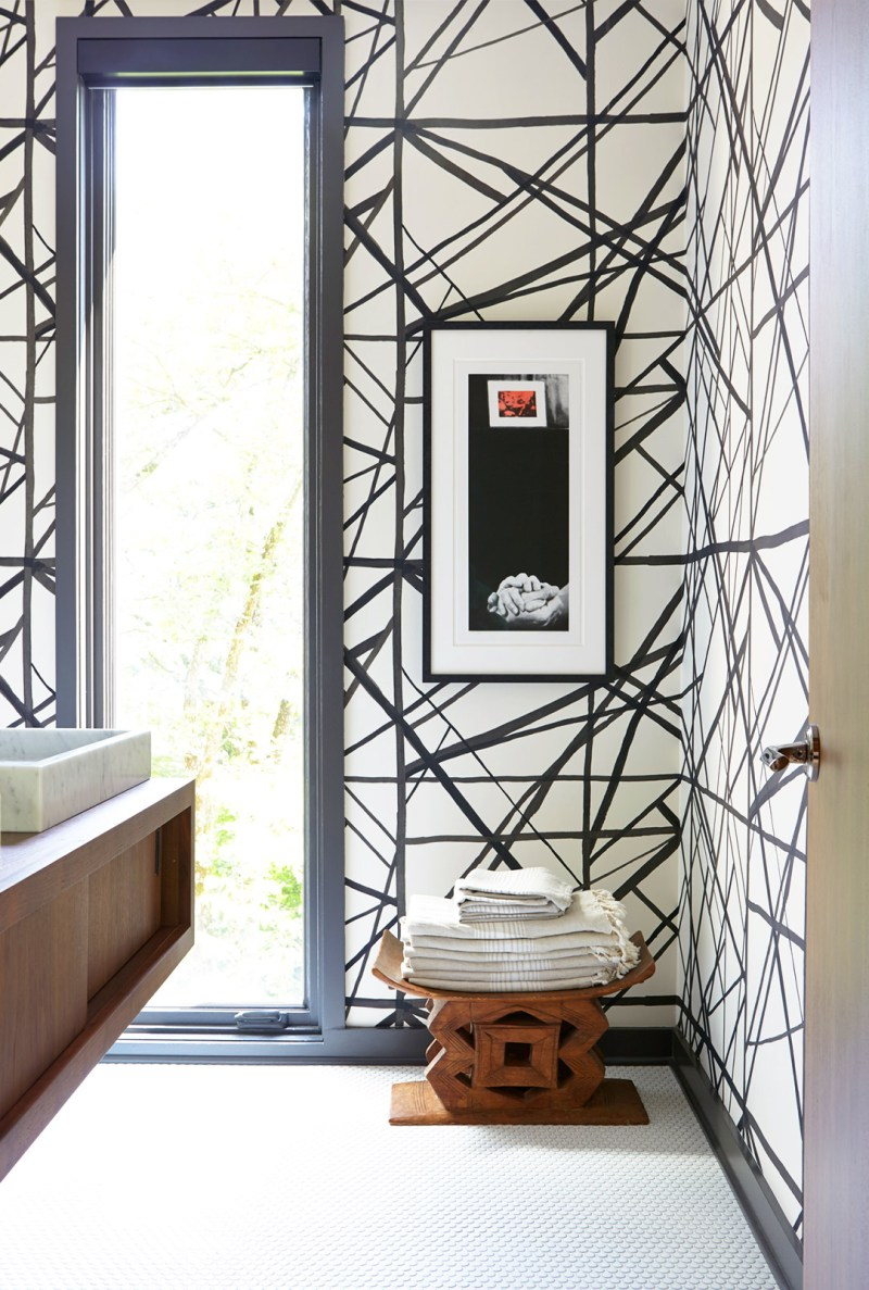 An incredible bathroom in this country house made modern with the geometric black and white wallpaper by Kelly Wearstler