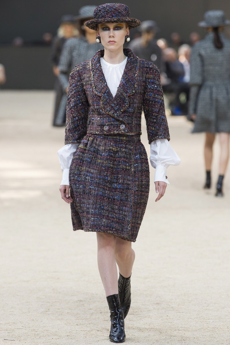 Model walking down runway at Chanel fall 2017 couture show in classic plaid dress with puff sleeves