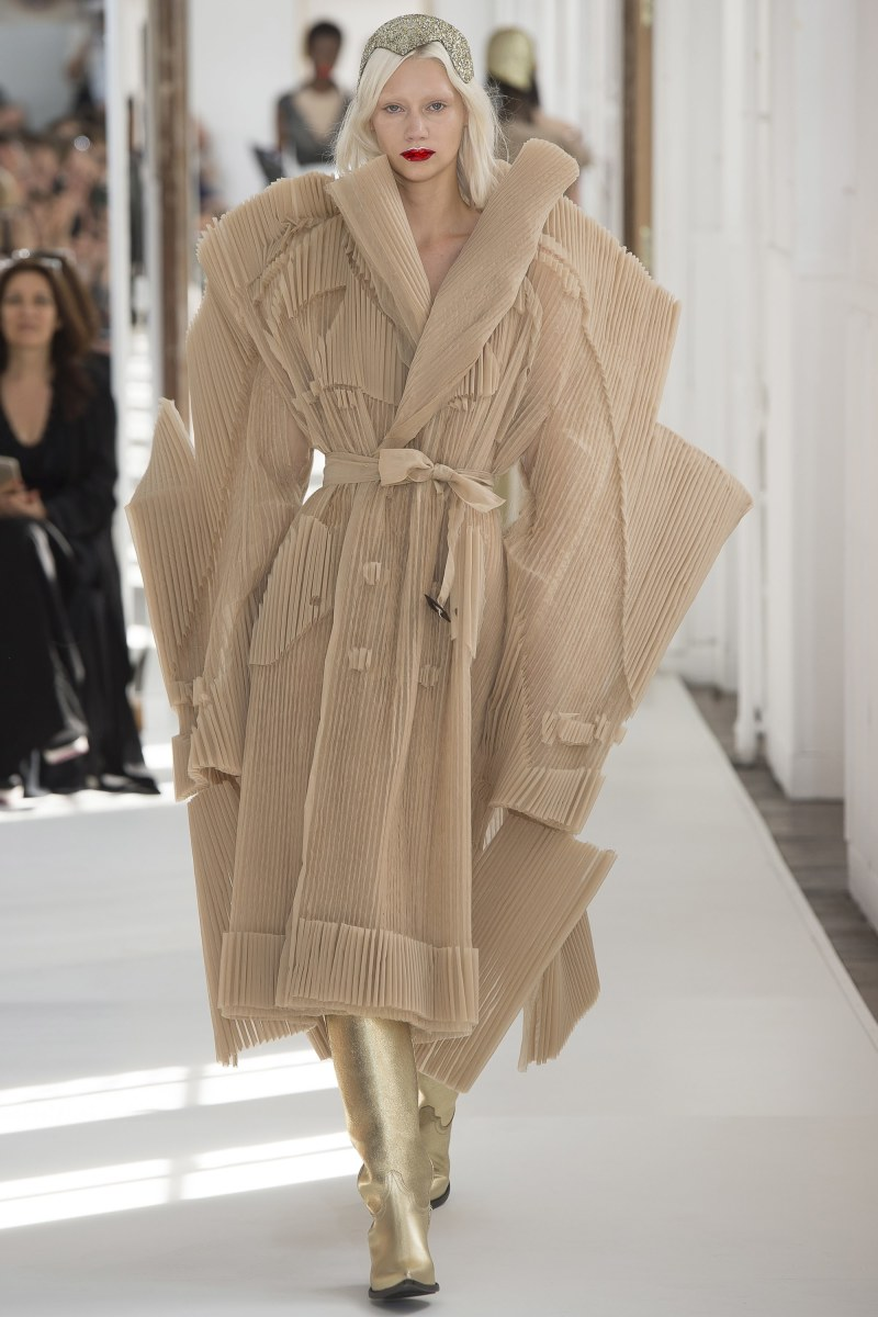 Model walking down the runway at margiela fall 2017 couture show in a dramatic trench coat dress