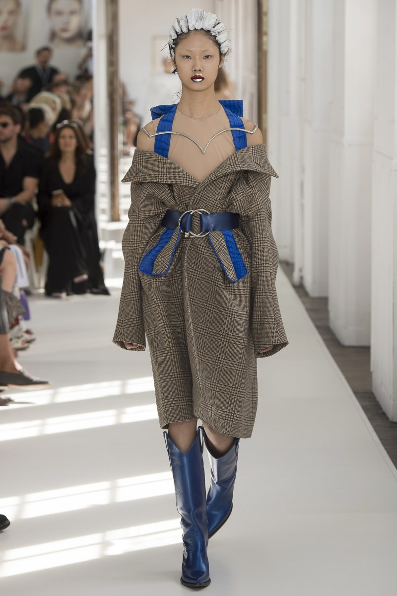 Model walking down the runway at margiela fall 2017 couture show in a belted trench coat dress