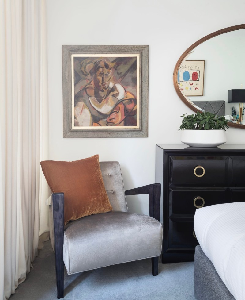 NYC apartment in soho furnished with gio ponti gray mohair chair, robsjon gibbings for witticomb, mid-century black lacquer dresser with succulent plant , custom bronze mirror and a custom upholstered bed by joe lupo with a joan miro lithograph