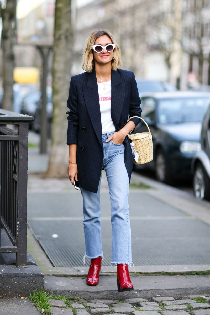 Street style shot of girl wearing red booties, jeans and blazer