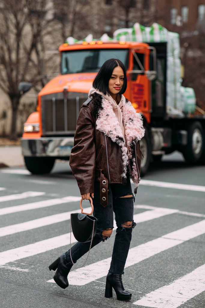 street style shot of street style shot of Tiffany hsu handinfire carrying a danse lente bag crossing the street at nyfw