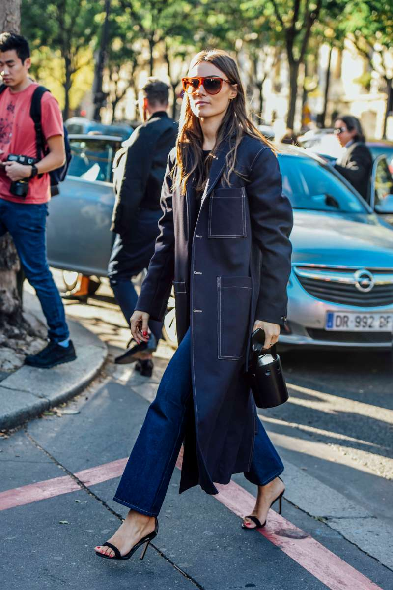 Giorgia Tordini in a Contrast Stitching jacket and jeans walking across the street