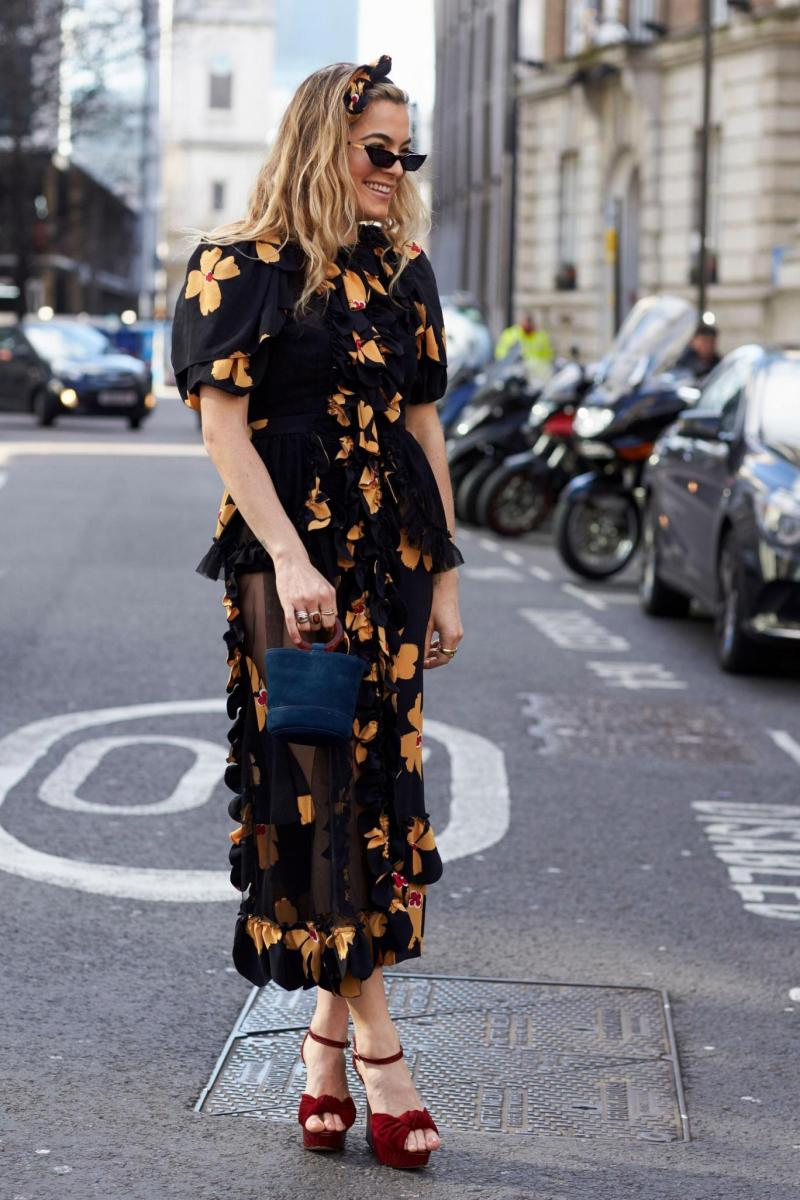 Street style shot of blogger attending london fashion week wearing tiny sunglasses, floral dress, simon miller bucket bag.