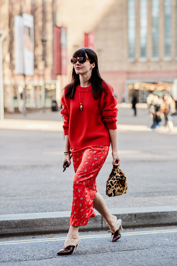 Street style shot of blogger attending london fashion week in red monochromatic outfit skirt and shirt