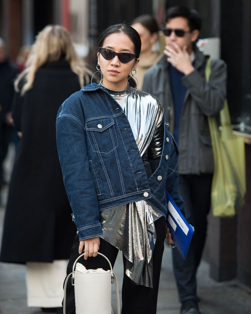 Street style shot of blogger attending london fashion week wearing tiny black sunglasses, jean jacket, metallic shirt, black pants and white bucket bag.