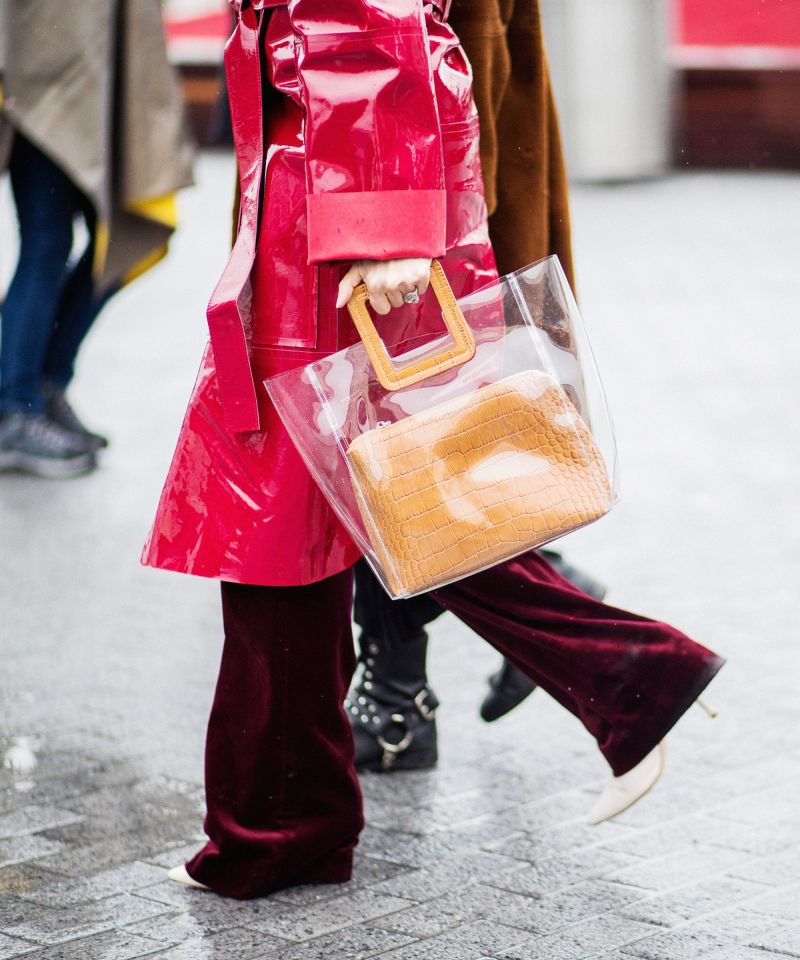 Street style image at fashion week of woman carrying the staud shirley clear plastic bag, pink vinyl raincoat and velvet pants