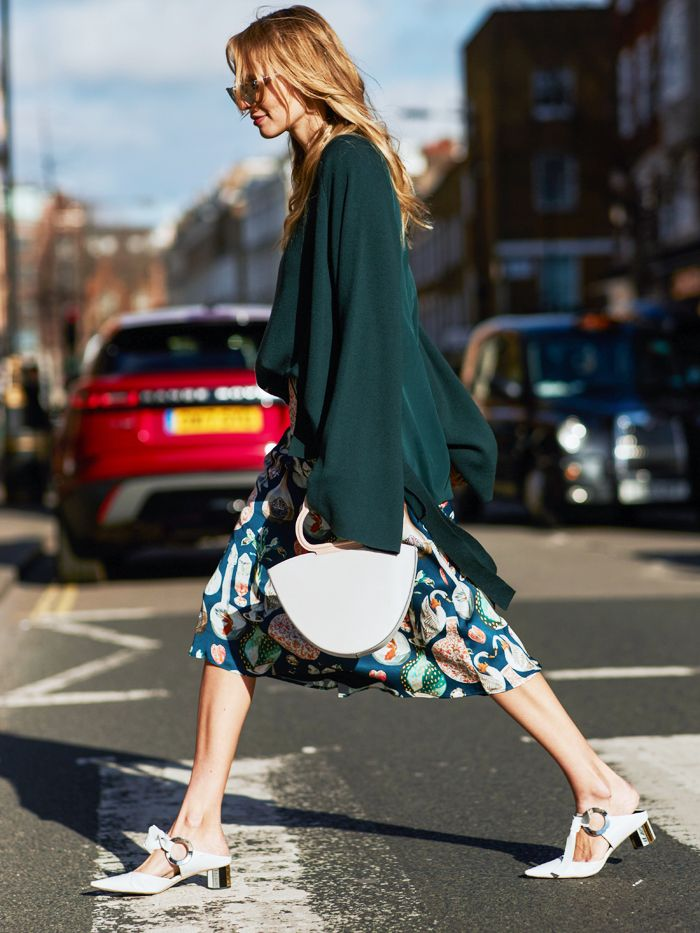 Street style shot of blogger attending london fashion week wearing a forest green sweater, printed skirt, white kitten heels and a white danse lente handbag