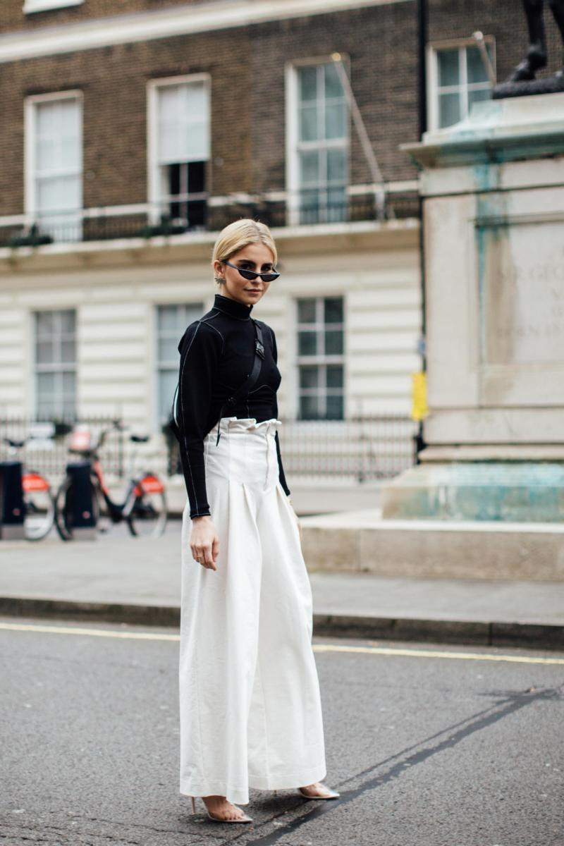 Street style shot of blogger attending london fashion week wearing tiny black sunglasses, black shirt and white pants
