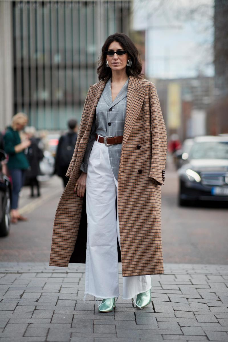 Street style shot of blogger attending London fashion week in a plaid coat, white pants and grey shirt