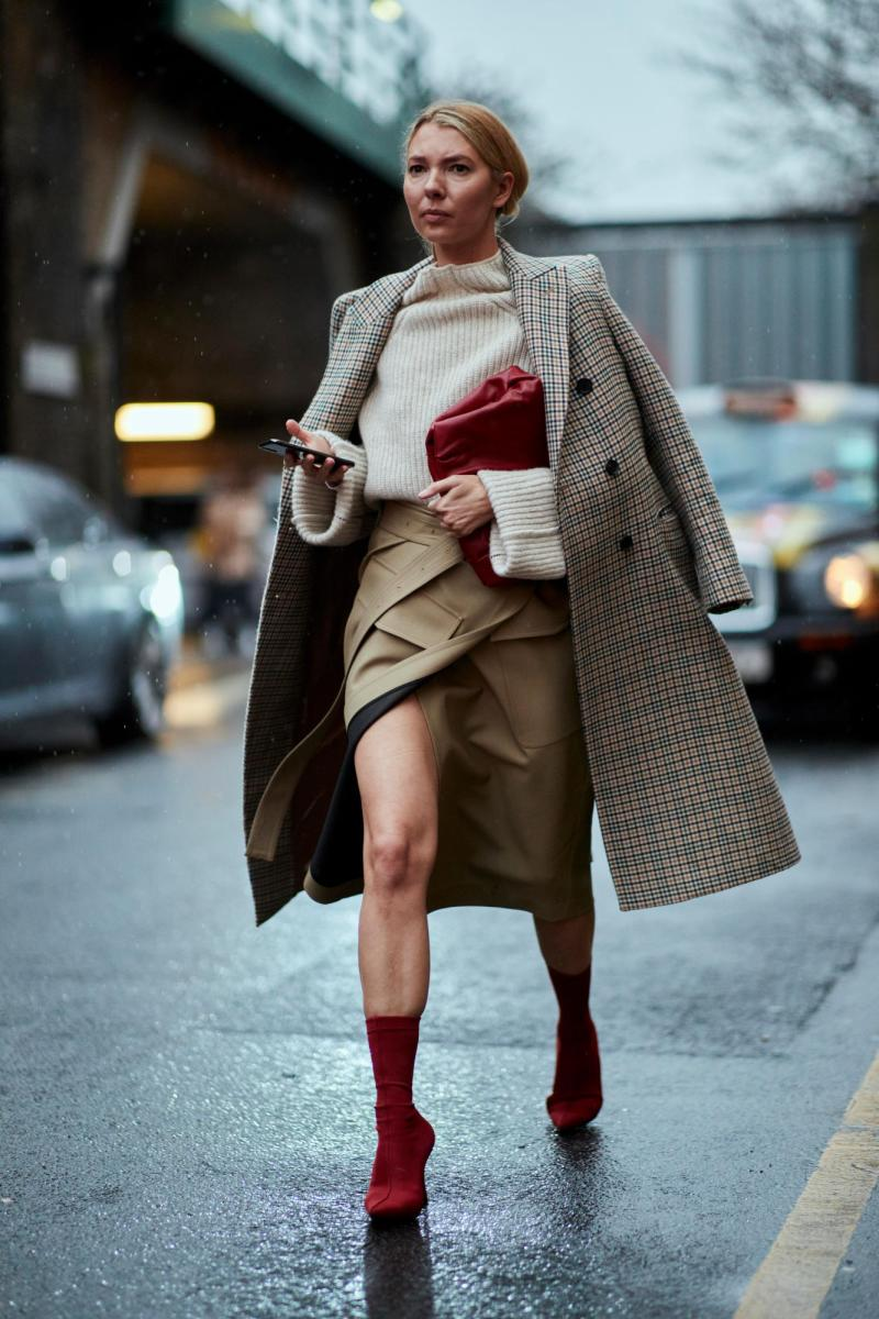 Street style shot of London fashion week in a plaid coat, beige sweater and olive green skirt
