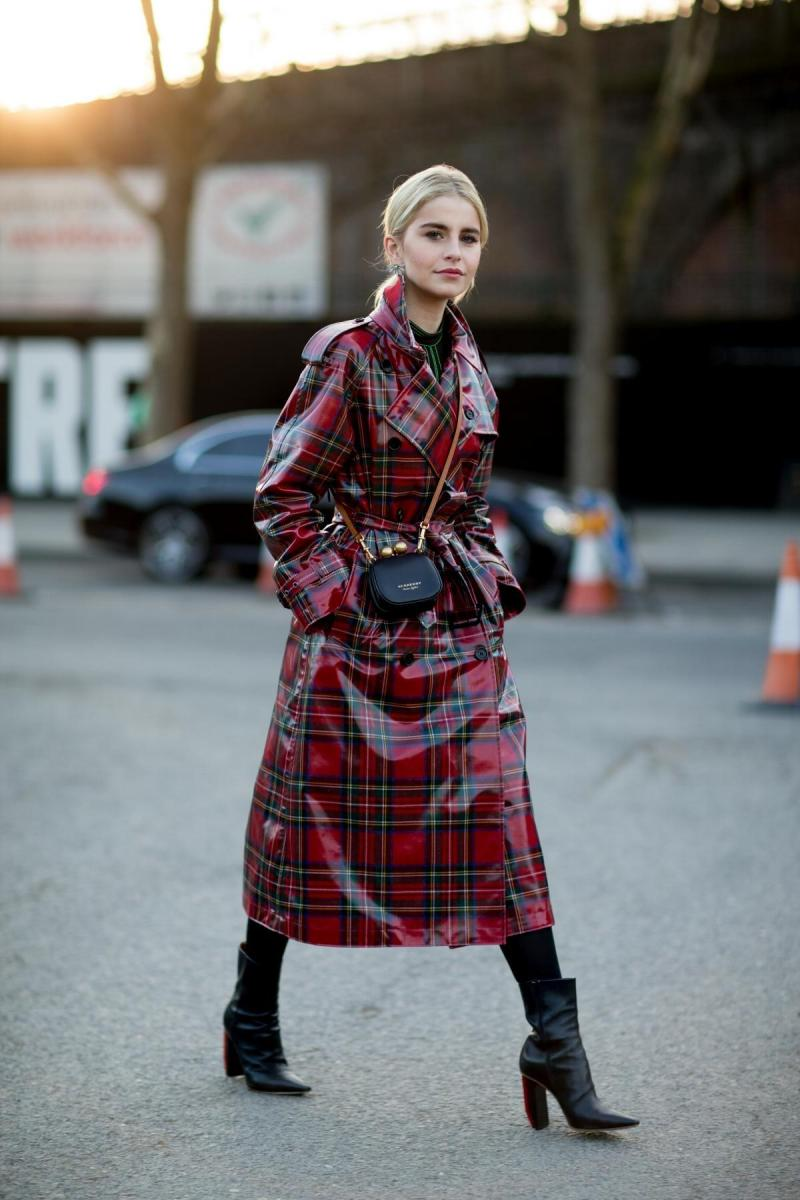 Street style shot of a blogger attending london fashion week wearing a red patent leather plaid trench coat