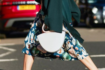 Street style shot of woman carrying a danse lente bag and wearing a printed skirt and kitten heels