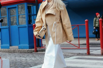 Street style shot of a girl wearing head to toe neutral clothing and a straw bag