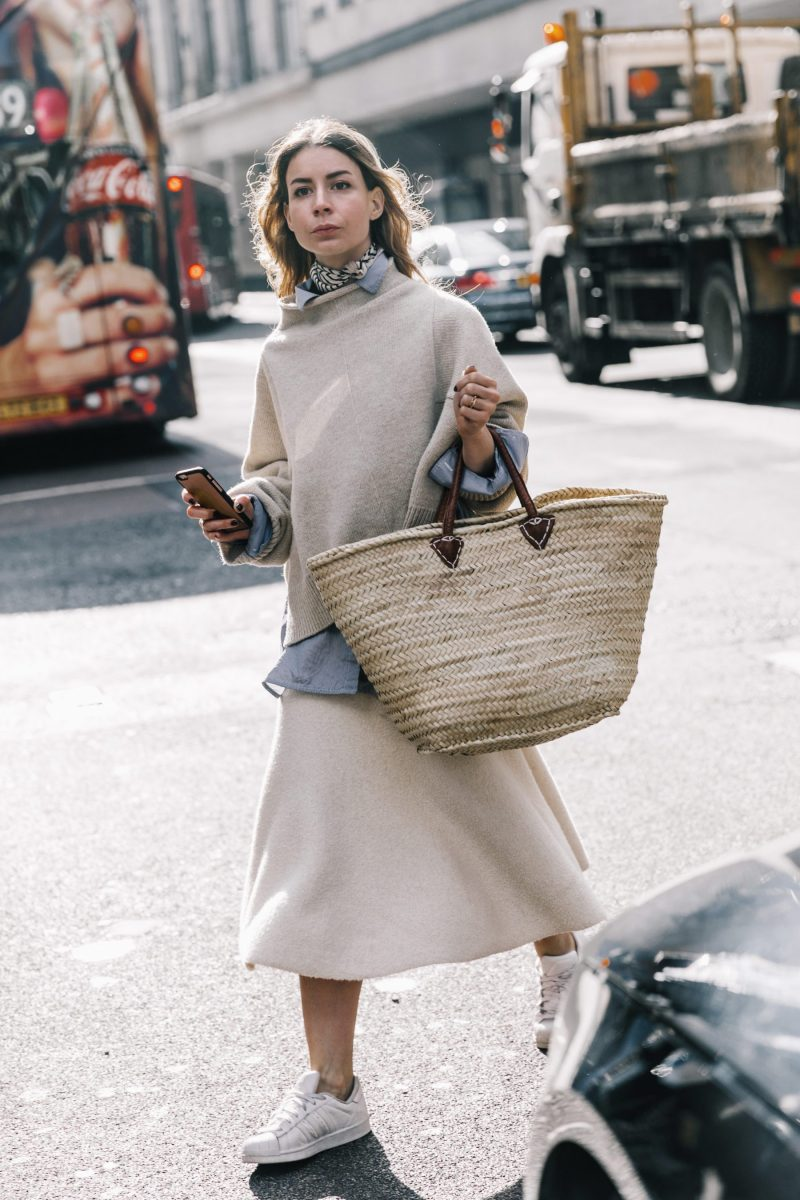 street style shot of woman crossing the street wearing an all neutral color outfit and carrying a straw tote bag