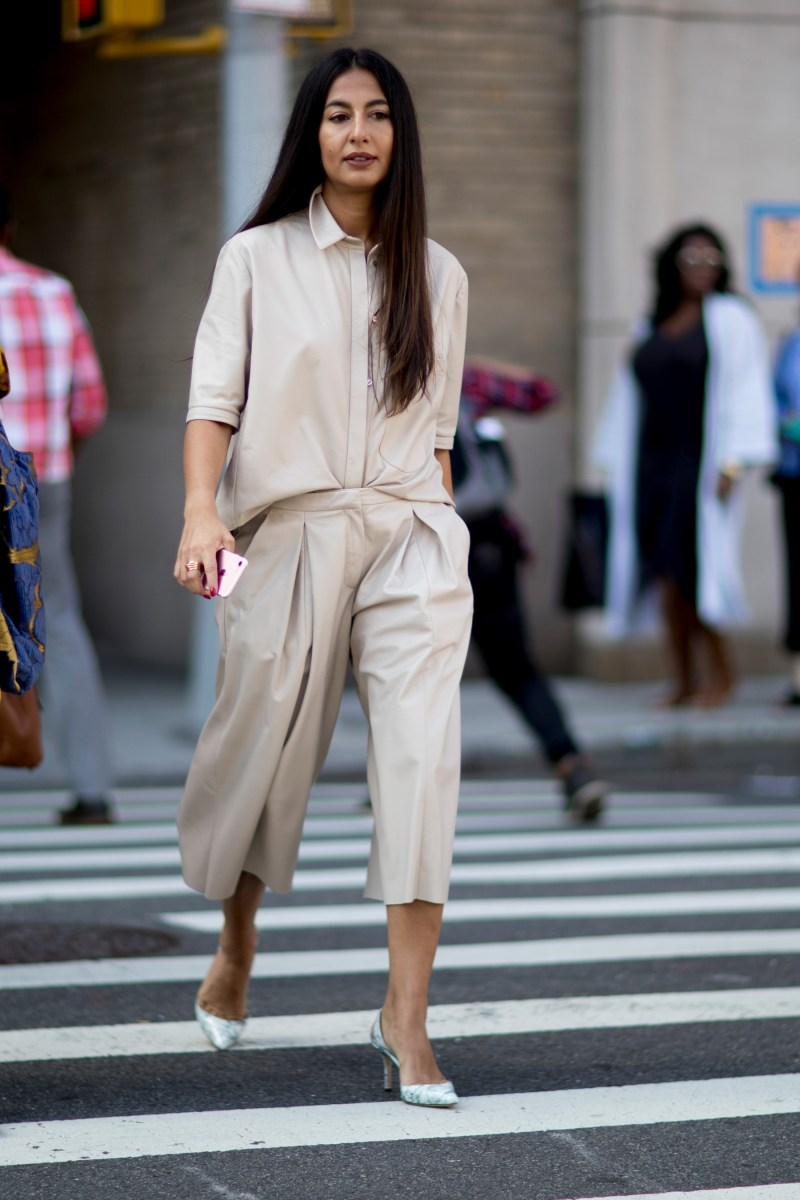 a street style shot of an editor at new york fashion week wearing a neutral outfit