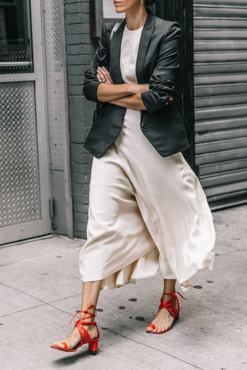 Photo of girl wearing strappy red celine sandals, a white dress and jacket