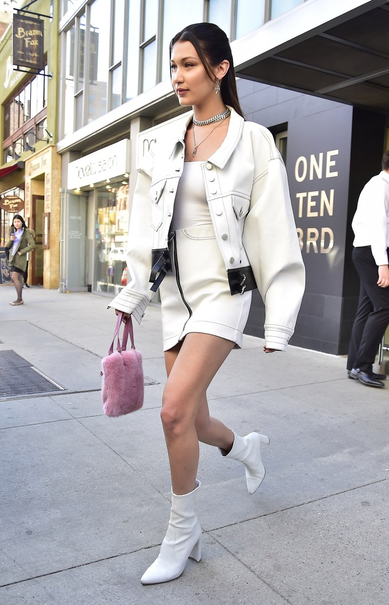 Bella Hadid in a white denim co-ord set and white booties walking in los angeles