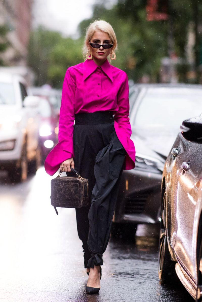 street style image of caroline daur walking to a fashion show in a magenta top and black pants
