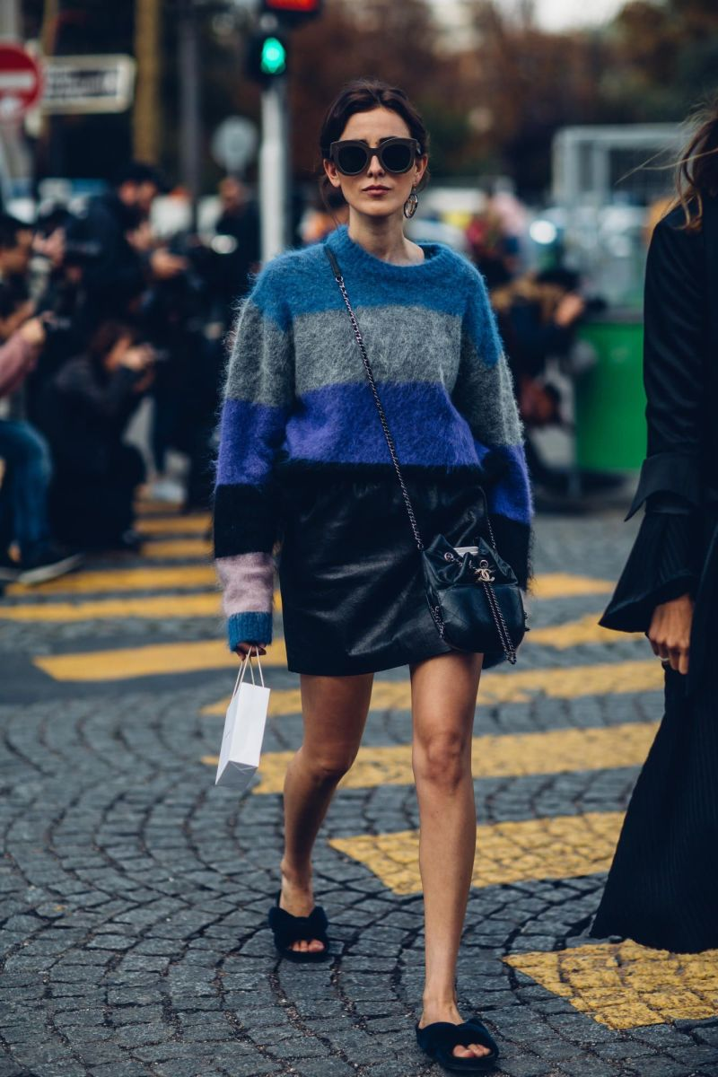 Street style shot of girl wearing mohair striped sweater and leather skirt