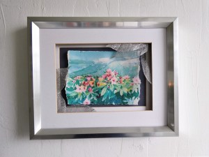 A watercolor painting of flowers in front of a mountain with silver leaves up front
