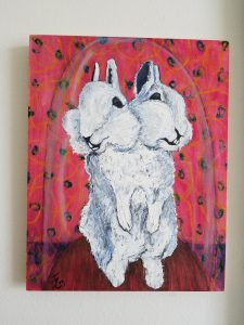 white bunny with two heads in front of a read patterned background