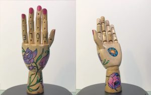"""A mannequin hand with painted flowers on it and letters on the fingers spelling out """"whole"""""""