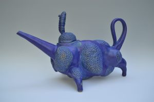 A blue teapot with lid