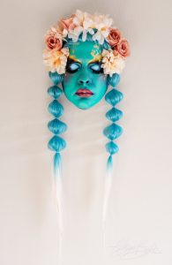 A sculpture of a woman's face with green blue skin and hair and pink and red flowers on her head