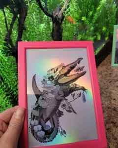 holographic gator in pink frame photographed in front of an aquarium