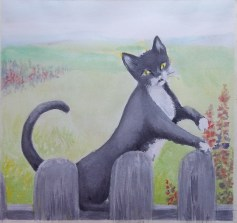 Weathered grey round top picket fence with tuxedo cat on the top back brace. An open green field with lupines and other wildflowers on bright day.