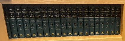 Green and black hardbound books on a wooden shelf, The Dictionary of Art